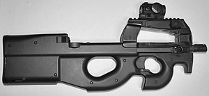 Bullpup - The FN P90 uses the bullpup layout in conjunction with a unique top-mounted feeding system, making it the most compact submachine gun with a fixed buttstock