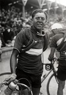 A man with a dirty face holding his bicycle, spare tires wrapped around his shoulders. In the background a large crowd.