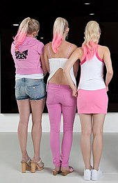 63b77d70517aad Models at an event in UK, wearing (from left to right)- shorts, trousers,  mini skirt.
