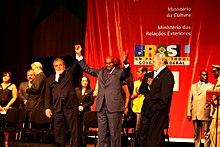 le président Wade du Sénégal et le président Lula da Silva du Brésil, se tiennent la main devant un affiche annonçant le festival des arts nègres de 2009, à Dakar