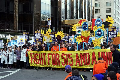 "Protesters call for an increased legal minimum wage as part of the ""Fight for $15"" effort to require a $15 per hour minimum wage in 2015. A government-set minimum wage is a price floor on the price of labour."