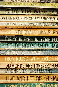 Fourteen Fleming Bond books in a pile, the titles visible on the spines