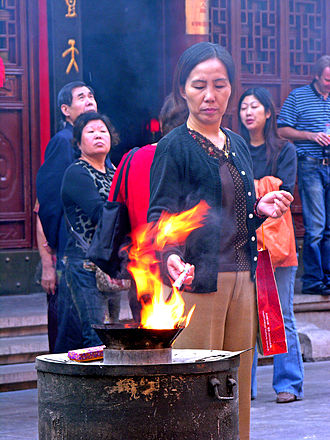 Jingxiang - Woman kindling the incense sticks for jingxiang at a temple in China.