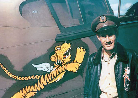 "Flight leader and fighter ace Robert ""R.T."" Smith stands next to his P-40 fighter at Kunming, China. The ""Flying Tiger"" insignia was created by the Walt Disney Company. Flying tigers pilot.jpg"