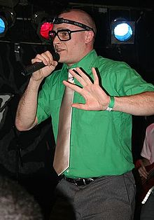 Photograph of a man in a green shirt holding a microphone.
