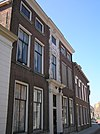 foto van Huize den Berg. Fors pand met vijf traveeën brede lijstgevel op natuurstenen, met zwart opgewerkte plint. Middentravee iets risalerend