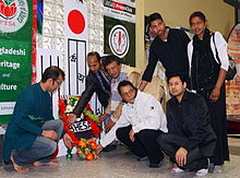 People laying flowers at a simple indoor shrine
