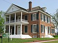 Large red brick home with two-story columned white porch