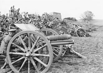 Honourable Artillery Company - Gunners of A Battery, the Honourable Artillery Company, attached to the 4th Australian Light Horse Brigade, crouch between their 13 pounder quick fire field guns and a cactus hedge near Belah, Palestine, in March 1918.