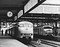 HUA-171408-Afbeelding van een electrisch treinstel mat. 1964 (plan T) langs het tweede perron van het N.S.-station Leiden te Leiden, met rechts een treinstel plan V.jpg