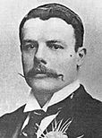 A black-and-white portrait of a white gentleman in a dark suit, a carnation prominent in his buttonhole. He has a square jawline and a handlebar moustache.