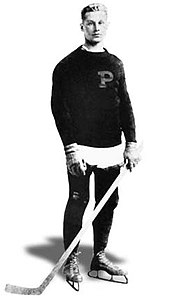 "Young man posing for a photo wearing skates and holding a hockey stick. He is also wearing a sweater with a large letter ""P"" on it"