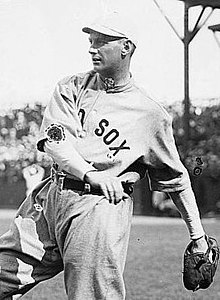 "A man wearing a baseball uniform with ""Red Sox"" displayed on the chest caught in the midst of throwing a baseball."