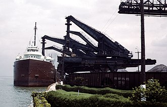 Hulett - Huletts at the PRR ore docks at Cleveland.  The near Hulett is discharging into the hopper, while the next is lowering its bucket into the hold.