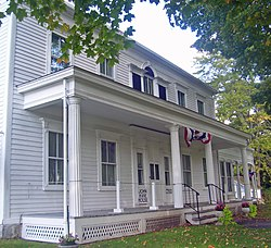 "A white house with porch and fluted columns decorated in red, white and blue bunting viewed from its left with some tree branches visible at the sides. A small sign near the front steps says ""John Kane House""."