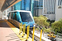 A people mover vehicle is pulling into an elevated metro station with large buildings in the background.