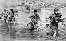 a black and white photograph of a line of males in uniform carrying weapons wading through a shallow river