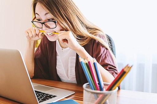 Laptop and girl biting pencil-pixabay