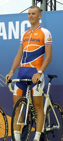 A road racing cyclist in an orange and blue jersey with white trim, standing over his bicycle which is stationary.