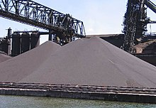 Large gray outdoor piles, surrounded by factory equipment