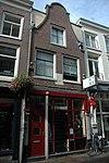 foto van Pand met ingezwenkte halsgevel, thans bestaande uit drie bouwlagen met kap loodrecht op de straat en een kelder met tongewelf