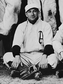 "A man sitting on the ground wearing a white baseball uniform with an ""A"" on the chest has his baseball glove placed at his feet."