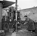 Man gooit kolen op het vuur van de distilleerketel, Bestanddeelnr 252-9467.jpg