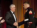 Marine Corps Sgt. Andrew C. Seif, right, shakes hands with Chariman, USO Board of Governors, Richard B. Myers, before receiving the USO Marine of the Year award from the Assistant Commandant of the Marine Corps 131025-M-KS211-017.jpg