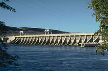 A concrete hydroelectric dam's spillway on the downriver side. Water is in the foreground and power lines run overhead.