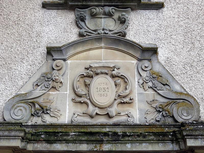 Iwwer dem Portal vun der Nikloskierch zu Housen. Um Medaillon: 1774 1951 1863