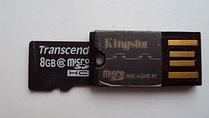 USB flash drive - A Kingston card reader which accepts Micro SD memory cards (Transcend card shown partially inserted), and acts as a USB flash drive; resulting size is approximately 2 cm in length, 1 cm in width, and 2 mm in thickness.