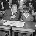 Minister- president Cals terwijl hij achter een lessenaar zit, naast een leerlin, Bestanddeelnr 918-3733.jpg