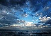 Sen utsikt over dagen ser langt ut over et hav fra en strand, som er utenfor synet utenfor bunnmargen.  Tre fjerdedeler av skuddet har en himmel preget av tungt skydekke, som skiller seg nær midten, og avslører en blendende lys ceruleanblå himmel som mørkner nær kantene.  Havet er striated med bølger som kommer parallelt med horisonten.