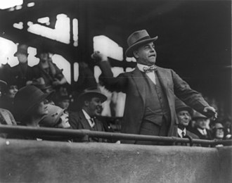 Congressional Baseball Game - Speaker Longworth throws out the first ball at the starting game at Griffith Stadium, Mrs. Longworth seated below, May 3, 1928.