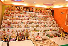 Colorful figurines displayed on white-sheeted shelves