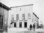 Nome post office on Second Avenue, with rug hanging out second-story window and two men walking by, Nome, Alaska, between 1900 (AL+CA 6374).jpg