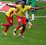 Two men wearing yellow shirts, red shorts and red socks, celebrating on a grass field