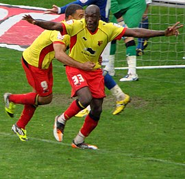 Two men wearing yellow shirts, red shorts and red socks, standing on a grass field. Both appear to be celebrating: one man has his arms aloft, the other is following him.