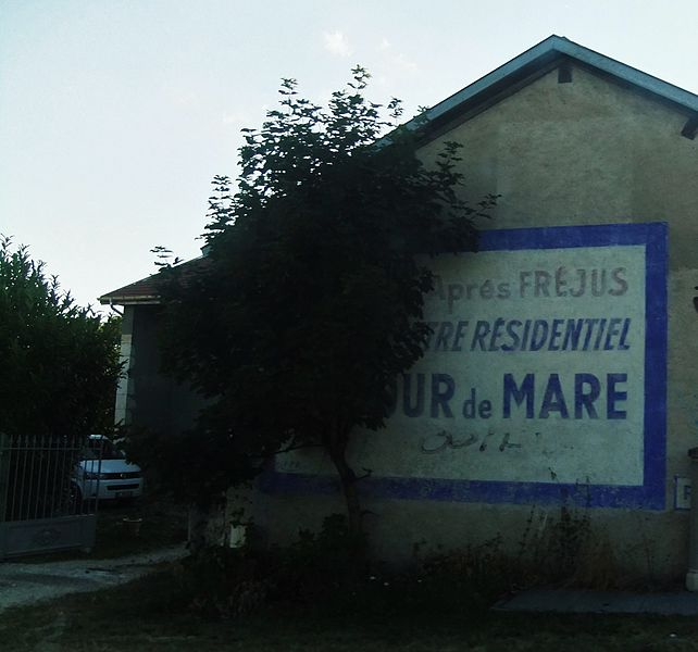 "Old painted advertisment for the then-new Tour de Mare residential development near Frejus, on the wall of a farmhouse in Cessy, France.  The full text (translated) reads as ""2 kilometres after Frejus, the Tour de Mare residential centre is waiting for you..."""