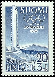 "A soild blue background is intruded on its left side by a structure, shaded in white, representing the tower and stand of the Helsinki Olympic Stadium. The Olympic rings, also white, lie at the top of the blue background, partly obscured by the stadium's tower. The word ""1952"" is written in white in the middle of the blue background, while ""XV Olympia Helsinki"" is written in blue, beneath the image."