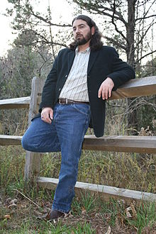Ronnie Penque, wearing blue jeans and a jacket and leaning against a wooden fence