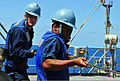 Petty Officer 3rd Class James Haynes, gunner's mate, right, and Petty Officer 3rd Class Casey McNeill, fire control man, heave a phone and distance line aboard amphibious dock landing ship USS 100930-N-KB563-070.jpg