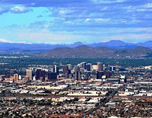 A photo showing the skyline of Phoenix, looking north. It shows the various buildings of the downtown area, as well as Sunnyslope Mountain in the background