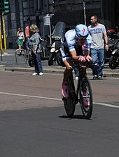 A road racing cyclist wearing a light blue skinsuit and matching aerodynamic helmet, with pink shoes and gloves. Spectators watch at the roadside.