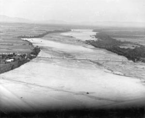 Burdekin Bridge - Aerial photograph of Burdekin Bridge construction site showing piers with Railway Bridge in foreground c 1952