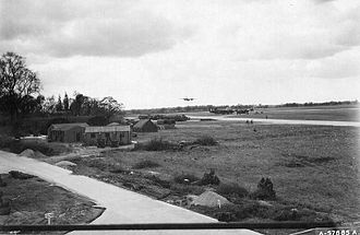 RAF Lavenham - A B-26 about to buzz Lavenham. View is to the west and the buildings at left are 839th BS offices. Two B-24's parked across field are said to likely be 42-94756 and 41-29488.