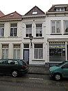foto van Huis met eenvoudige geelgepleisterde lijstgevel en schilddak