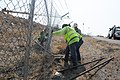 Repairing security fence at construction site (9401475093).jpg