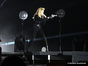 """Revolver (song) - Madonna holding a fake gun while performing """"Revolver"""", during The MDNA Tour in 2012"""