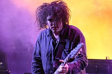 Head and shoulders shot of man, with wild, tangled hair and lipstick on,  playing in a stage spotlight.